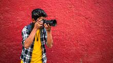 Joven Fotógrafo Latino Cámara En Mano  Con Fondo Rojo