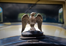 Metal Eagle Hood Ornament On Top Of Vintage Beige Car