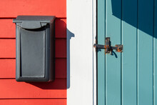 The Exterior Wall Of A Red Wood Building With A Teal Green Wooden Vintage Door. The Storm Door Has A Black Metal Rusty Latch. A Black Vertical Letterbox Is On The Wall Next To The White Door Trim.