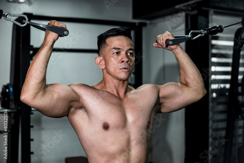 Wallpaper Mural A fit asian man does some standing cable double bicep curls at the gym