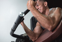 A Passionate And Fit Man Does Some Machine Preacher Curls At The Gym. Low Angle Shot. Arm And Bicep Workout Training.