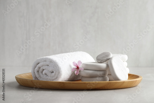 Spa stones, towel and fresia flower on light table