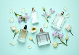 Fototapeta Kawa jest smaczna - Flat lay composition with different perfume bottles and flowers on cyan background