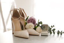 Composition With Engagement Ring And Wedding Shoes On Light Grey Table, Closeup. Bride Dressing