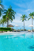 Beautiful Tropical Beach And Sea With Umbrella And Chair Around Swimming Pool In Hotel Resort