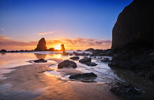 Wintry Sun Sets Behind The Needles At Haystack Rock, Cannon Beach, Oregon, At Low Tide