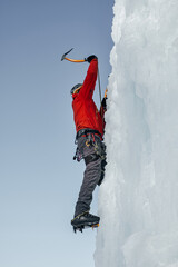ice-climber man with ice tools axe climbing a large wall of ice. Ou