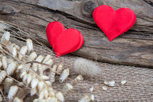 Two Red Hearts On Natural Wooden And Burlap Background. Valentine Day Greeting Card. Eco Friendly Concept.