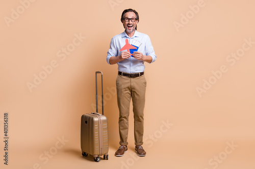 Full length photo of guy luggage hold paper plane tickets passport wear specs shirt pants shoes isolated beige color background