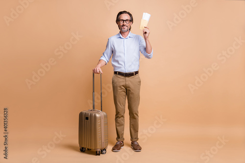 Full length body size view of nice cheerful man holding documents departure abroad isolated over beige pastel color background