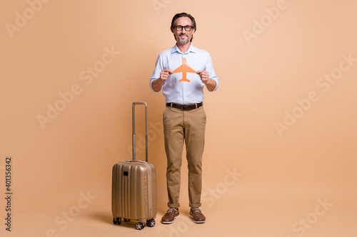Full length photo of bearded man baggage hold paper plane shape wear specs shirt pants shoes isolated beige color background