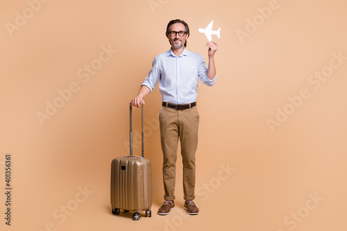 Full length photo of guy hold big case paper plane figure wear spectacles shirt pants footwear isolated beige color background