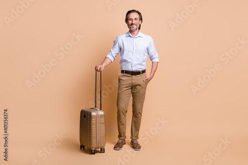 Full length photo of man hold big case hand pocket wear eyeglasses shirt trousers shoes isolated beige color background