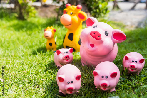 The family of pink pig doll statues that smiling and happy faces are placed on a green lawn Fototapete