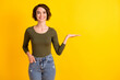 Photo of positive lady hold hand empty space for sale adverts promotion isolated over bright yellow color background