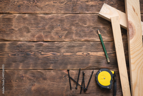 Obraz Screws, meter, pencil and wooden bars on the carpenter workbench background flat lay. - fototapety do salonu