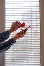 Sending Love Message Concept. Red Heart And Mobile Phone In Hand. Venetian Blinds In The Background. Modern Hipster Lifestyle