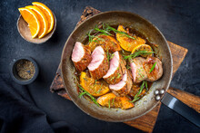 Traditional Fried Pork Filet Medaillons In With Orange Slices And Herbs Offered As Top View In A Rustic Wrought Iron Skillet