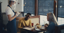 Waitress In Self Protection Serving Diverse Couple In Cafe