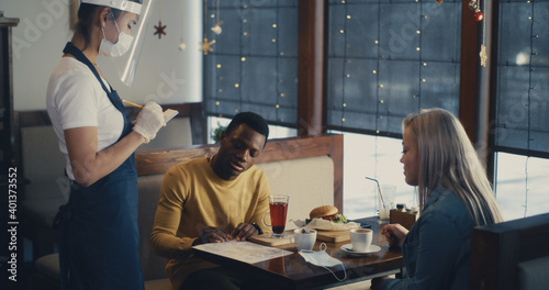 Fototapeta Waitress in self protection serving diverse couple in cafe obraz