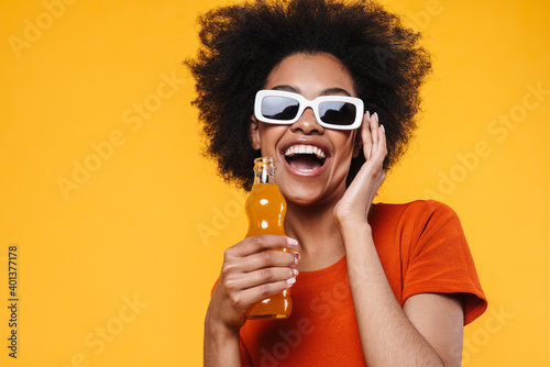 Canvas Print Joyful african american girl in sunglasses drinking soda and laughing