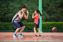 Happy Father And Daughter Playing Basketball On Playground