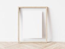 Blank Vertically Oriented Rectangular Picture Frame With Light Wood Border Standing On Wooden Floor Leaning On White Wall. 3D Illustration.