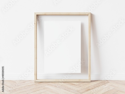 Obraz Blank vertically oriented rectangular picture frame with light wood border standing on wooden floor leaning on white wall. 3D Illustration. - fototapety do salonu