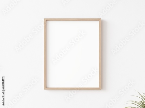 Obraz Single empty vertically oriented rectangular picture frame with thin wooden border hanging on white wall. 3D illustration. - fototapety do salonu
