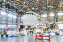 Aircraft Inside The Aviation Hangar, Maintenance Service. Airplane Technician Worker Working Around. Bright Light Outside The Gate.