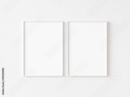 Obraz Two blank vertically oriented rectangular picture frames with thin white border hanging on white wall. 3D illustration. - fototapety do salonu