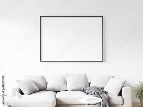Fototapeta Horizontally oriented rectangular picture frame with thin black border hanging on white wall above sofa in living room. 3D illustration. obraz