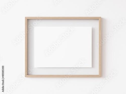 Fototapeta Empty horizontally oriented rectangular light wood picture frame hanging on white wall. 3D Illustration. obraz