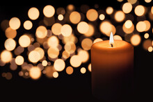 White Candle On A Black Background With Gold Bokeh. The Candle Flame Illuminates The Space Around Her. The Image Is Suitable For A Holiday Card.