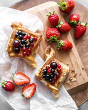 Two Freshly Baked Pastry Puffs With Cream Filling, Berry Topping And Strawberry On Paper And Wooden Table. Delicious Breakfast Concept. Homemade Dessert. Rustic Food. Top View
