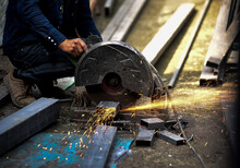 Mechanic Is Cutting Steel Metal With Rotating Steel Cutter Machine And Sparks Fly Out Within Steel Industry