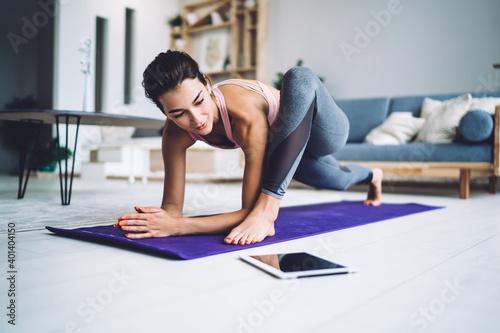 Slim woman stretching legs during yoga class Fototapeta