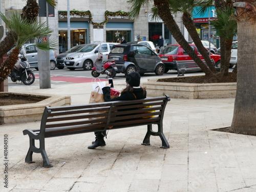 Obraz na plátně Signora con pacchi di regali natalizi seduta sulla panchina, mentre guarda il suo cellulare