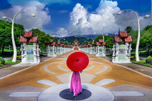 Thai Woman With  Umbrella Walks To See Ho Kham Luang Pavilion At Royal Park Rajapruek In Chiang Mai, Thailand.