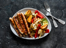 Grilled Turkey Sausages And Roasted Vegetables On A Dark Background, Top View. Delicious Lunch, Tapas, Appetizer