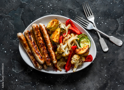 Canvas Print Grilled turkey sausages and roasted vegetables on a dark background, top view