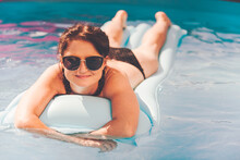 Young Woman On Pool Air Mattress In Above Ground Pool. Lifestyle At Home Concept.