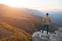 Man In Shirt Admires Sunrise Over Mountains With Coloured Forests And Fields Standing On Brown Rocky Hilltop Edge In Autumn Backside View