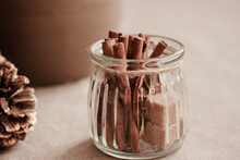 Cinnamon Sticks And Cubes Of Brown Sugar In Glass Jar, Tree Cone On Brown Background. Light And Shadow. Close Up