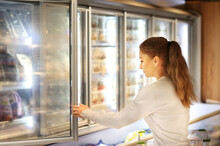 Woman Choosing Frozen Food From A Supermarket Freezer..