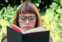Close-up Portrait Of Blue-eyed Caucasian Blonde Young Woman With Glasses Reading A Book In The Park