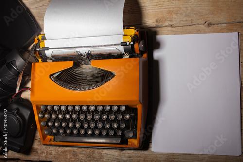Obraz na plátně Máquina de escribir vintage con papeles sobre un escritorio de madera rustica