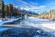 Frozen River Ice And Distant Snowy Mountain Peaks Landscape In Canadian Rockies, Banff National Park