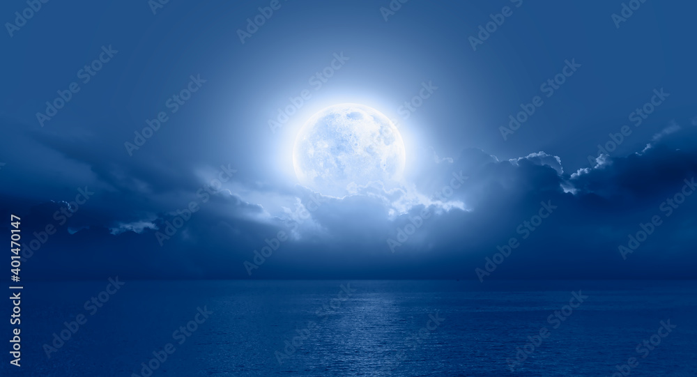 Fototapeta Night sky with moon in the clouds on the foreground blue sea