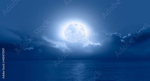 Fotografie, Obraz Night sky with moon in the clouds on the foreground blue sea Elements of this i